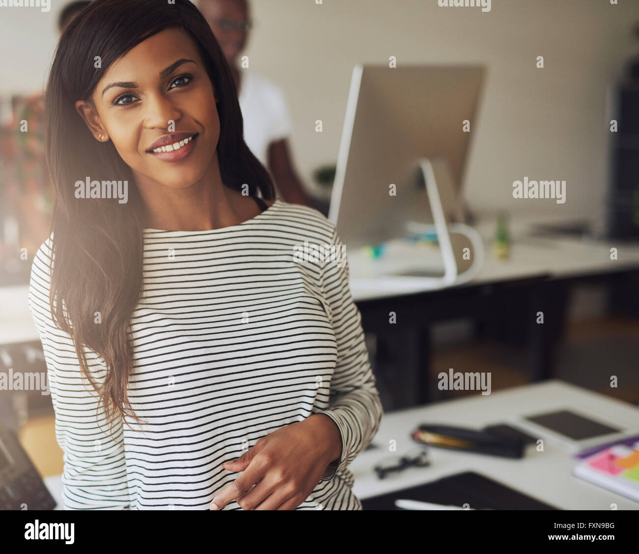 Single gorgeous female business owner wearing black and white striped blouse with partner on computer in background Stock Photo