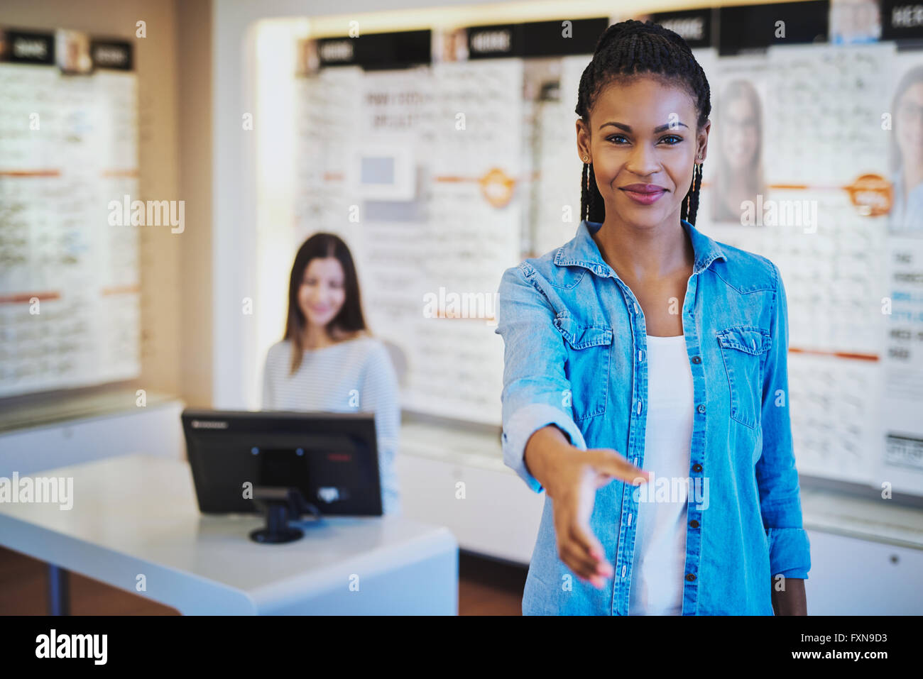 Young African woman welcoming you to her optometry store with an outstretched hand and friendly warm smile - Stock Image