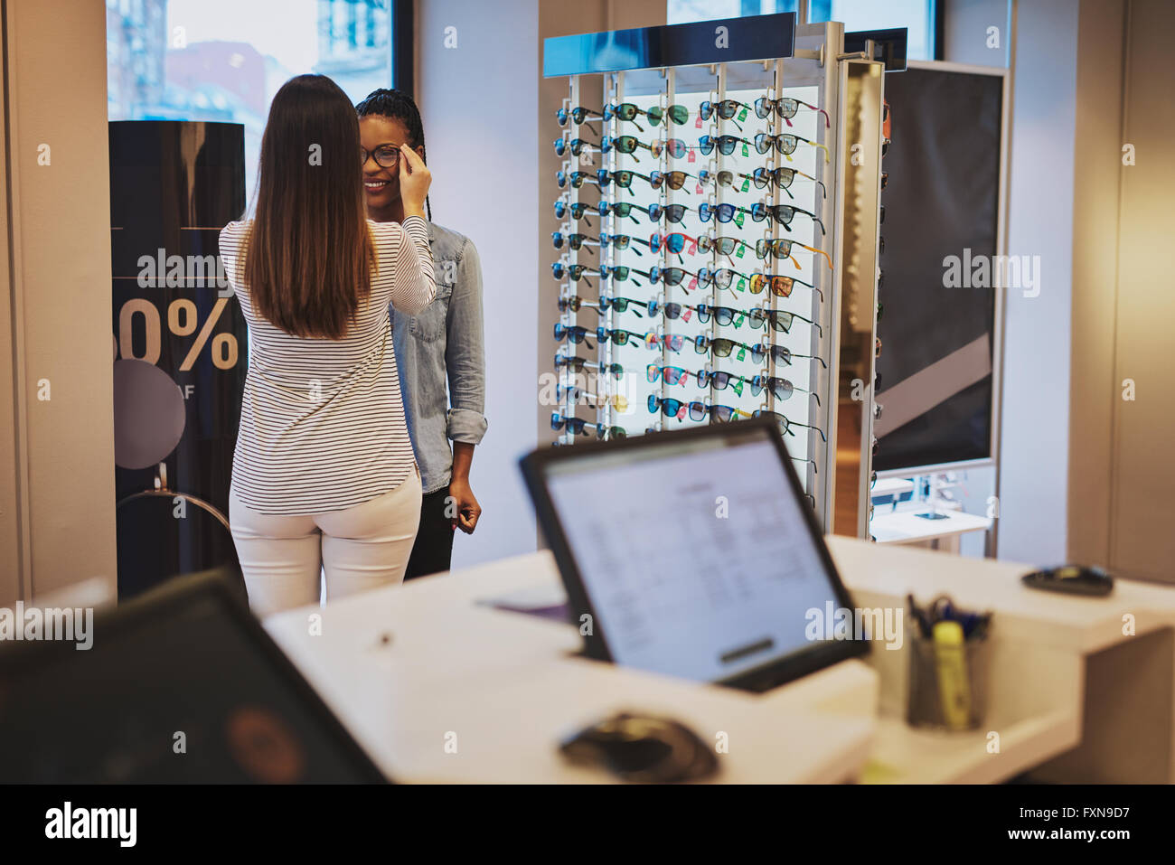 Saleslady assisting a customer in a store trying on eyeglasses with a view of a computer terminal in the foreground - Stock Image