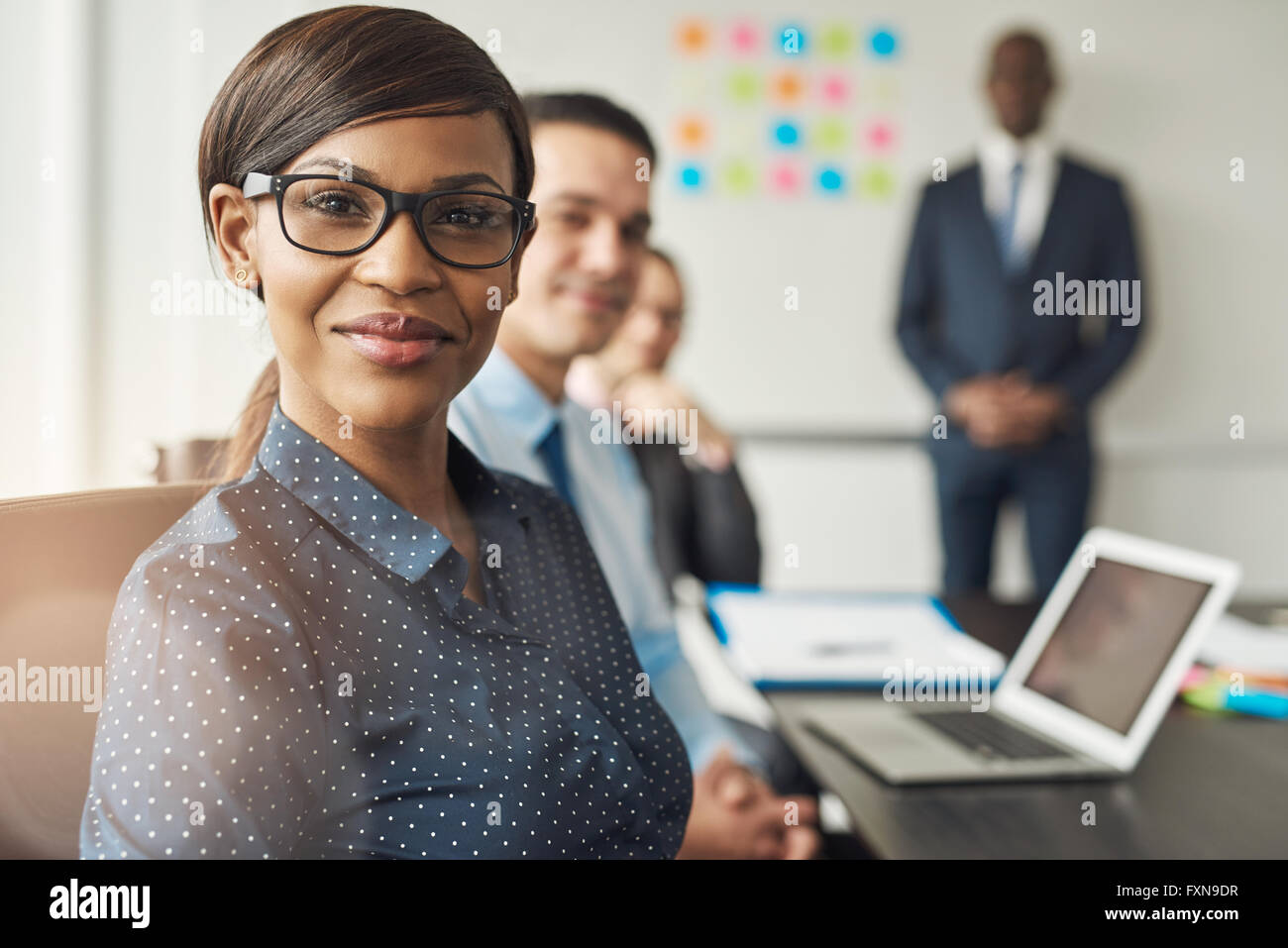 Beautiful cheerful professional woman wearing eyeglasses seated with male co-workers and team leader in conference - Stock Image