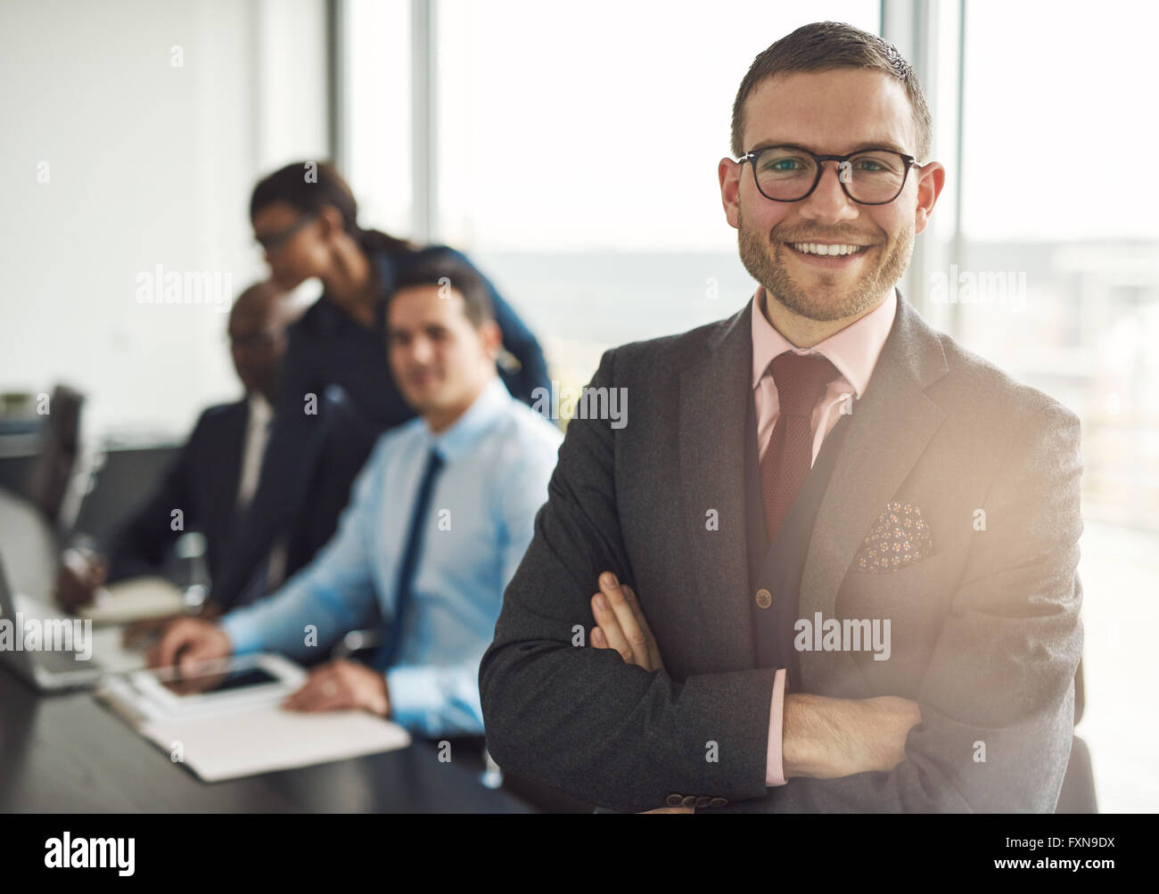 Confident smiling business executive with folded arms near conference table with three co-workers discussing something - Stock Image