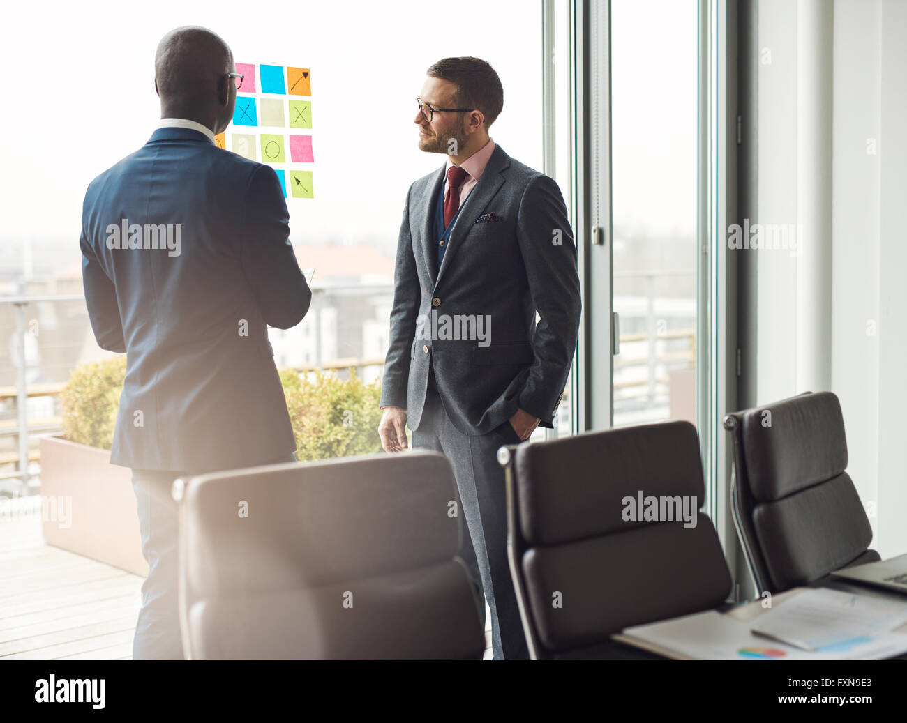 Two business man in stylish suits standing having a discussion in the office looking at a colorful array of sticky - Stock Image