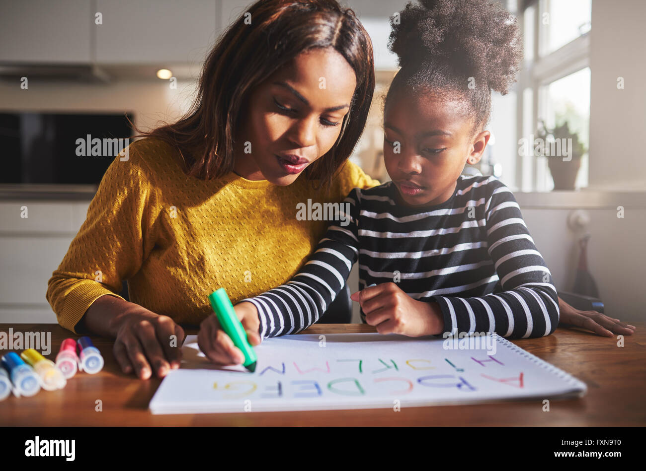 Black mother and child doing homework, learning the alphabet - Stock Image