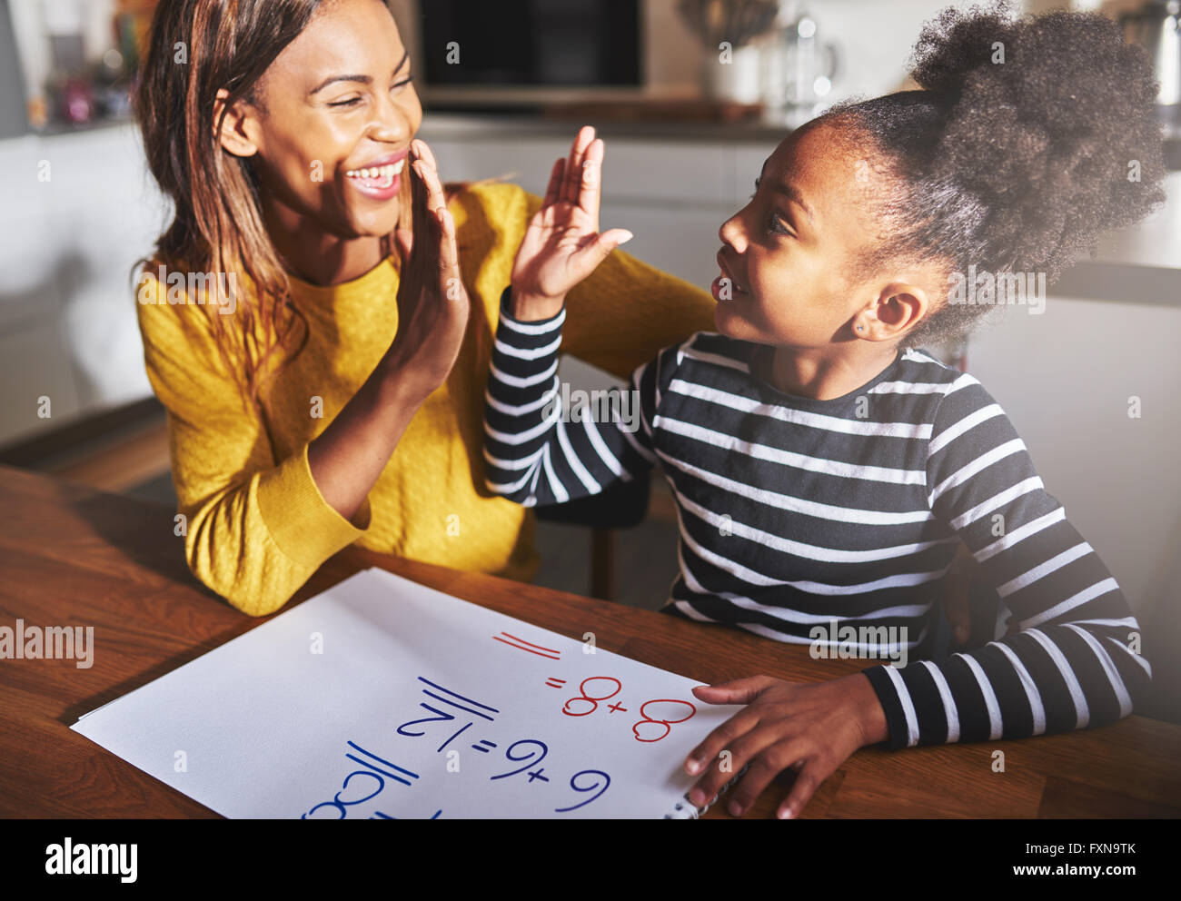 Learning to calculate, high five success, black mother and child - Stock Image