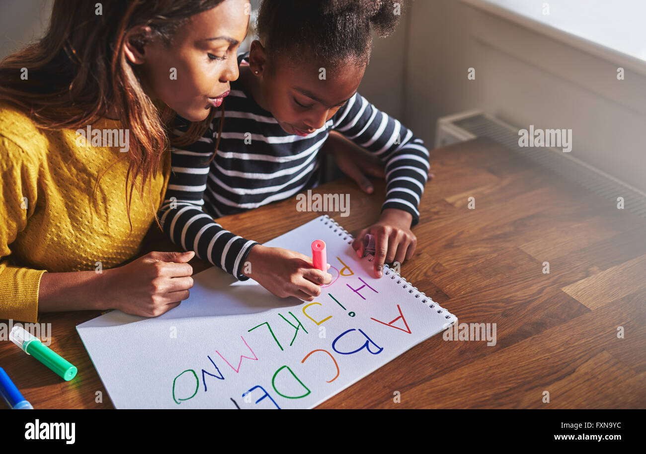 Learning the alphabet at home with her mom, black mother and child - Stock Image