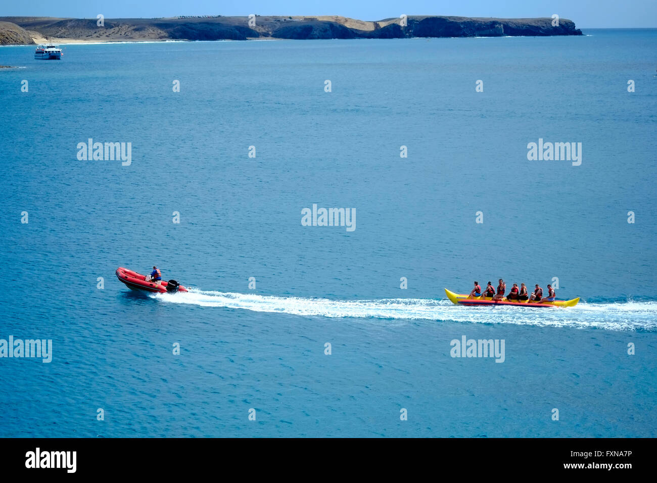 Holidaymakers enjoying a ride on a banana boat on the sea - Stock Image