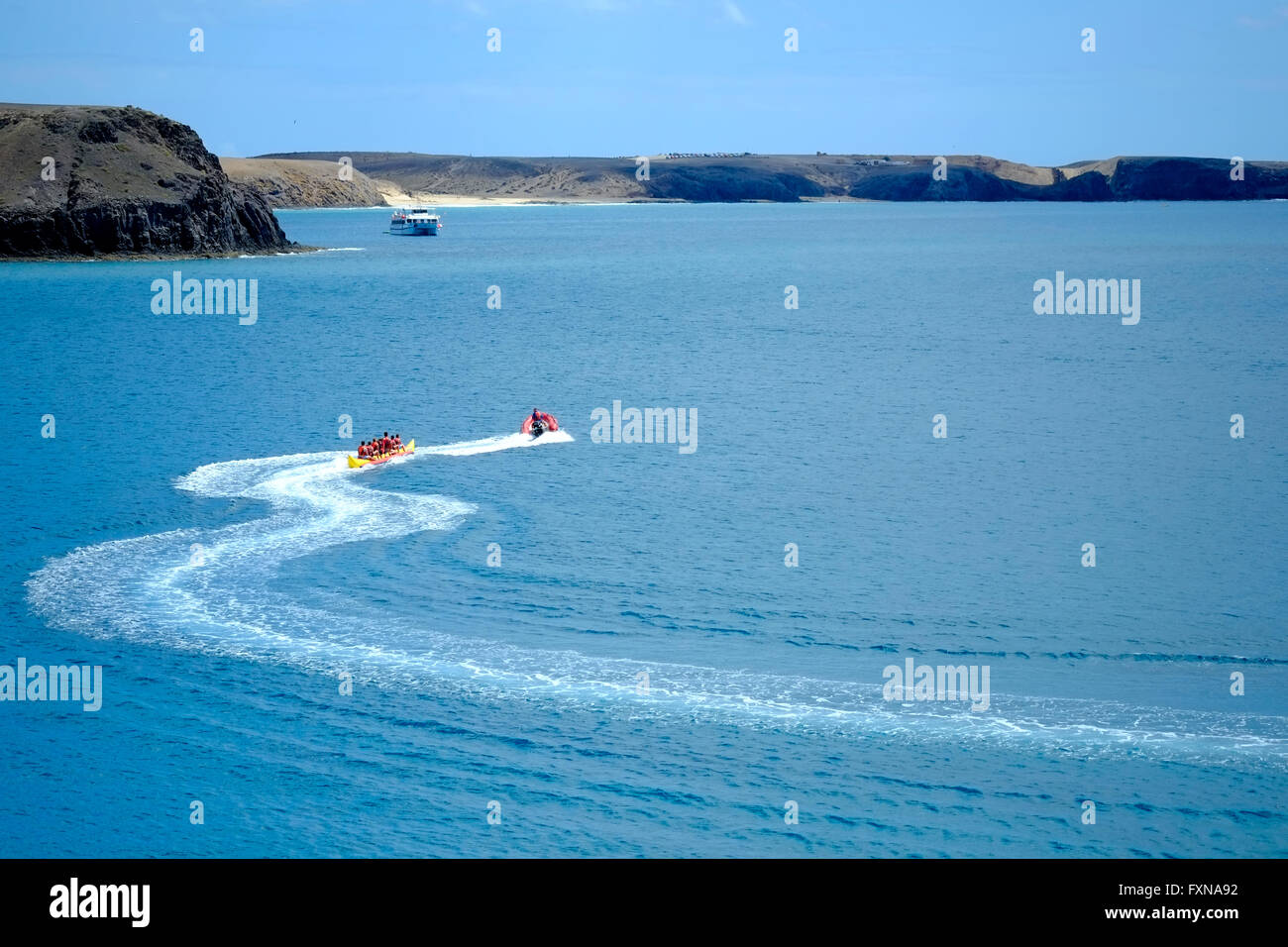 Holidaymakers enjoying a ride on a snaking banana boat on the sea - Stock Image