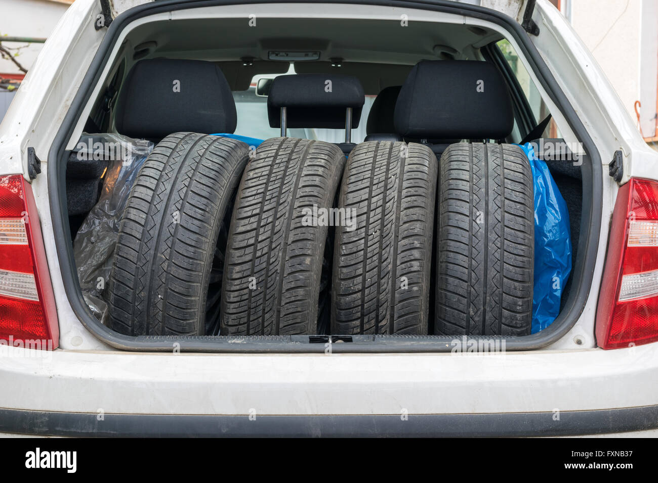 Tires prepared in trunk ready for seasonal changing, replacement - Stock Image