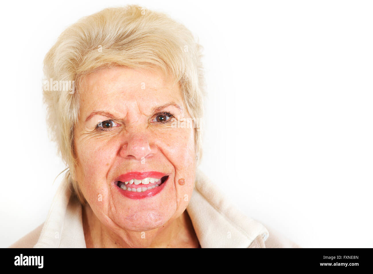 Blonde hair mature woman in her 70's smiling at the camera. - Stock Image