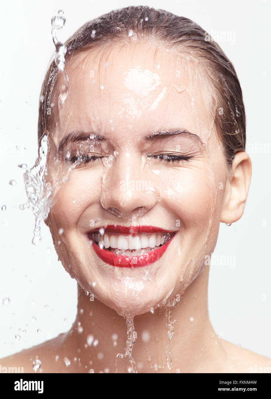 Smiling woman with water dripping over her face - Stock Image