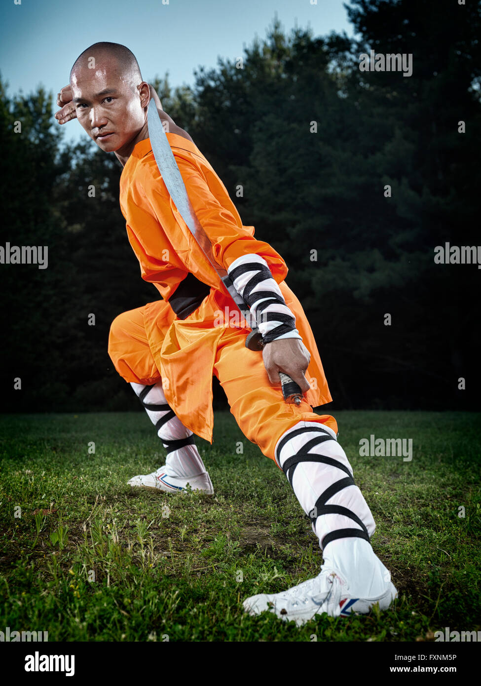 Shaolin warrior monk with a broad sword outdoors - Stock Image
