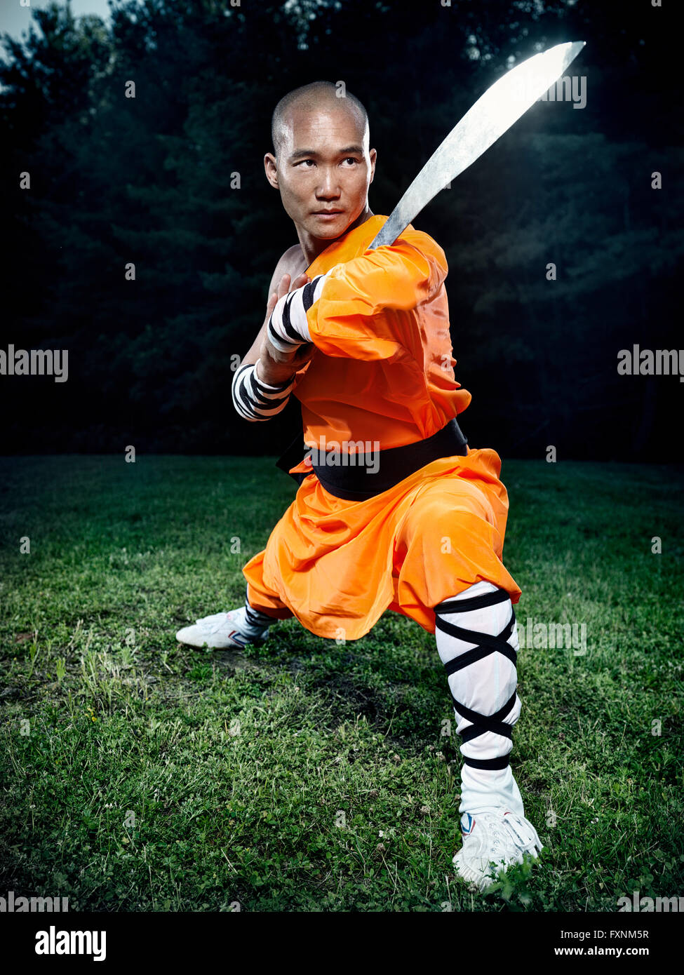 Shaolin warrior monk in a gong bu stance with a broad sword practicing Kung Fu outdoors - Stock Image