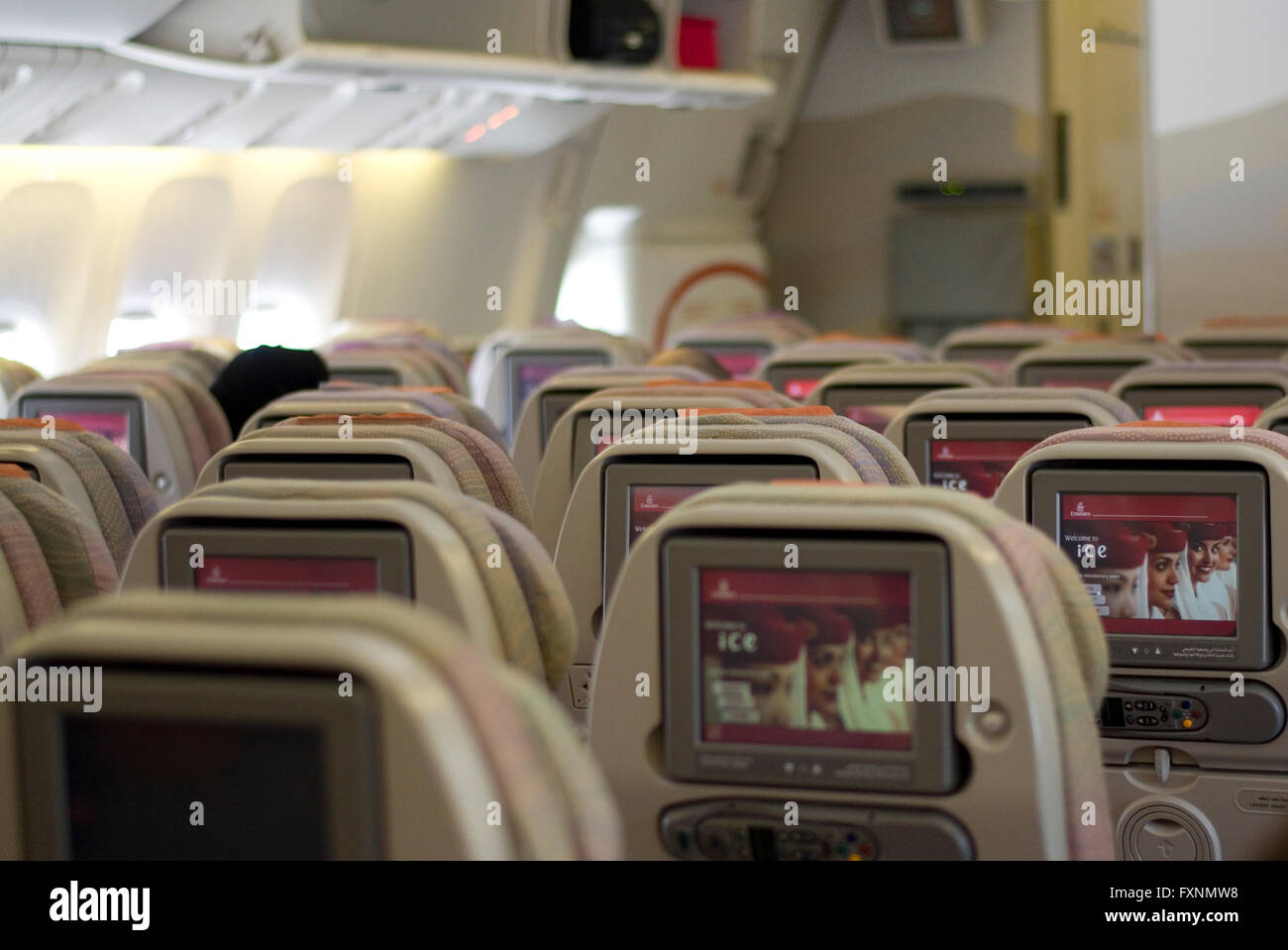 Entertainment screens in the back of seats in a Boeing 777-300 operated by Emirates. - Stock Image