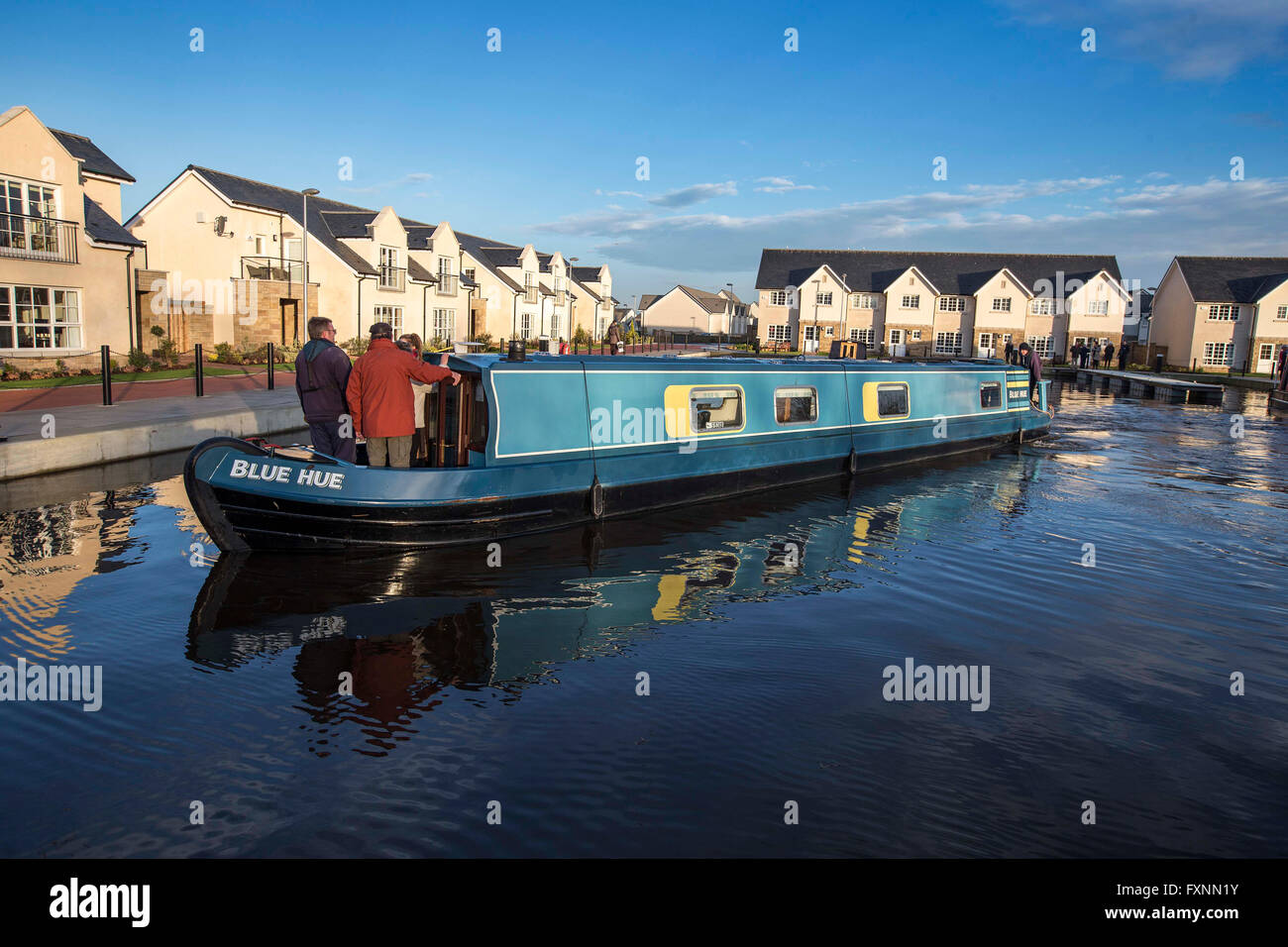 House boat entering basin with other houses reflected in water - Stock Image