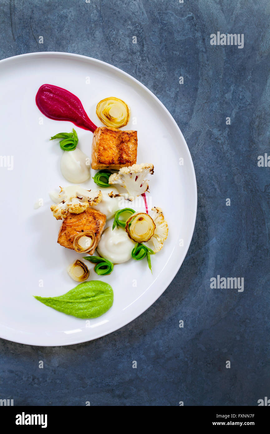 Pan fried salmon, pea puree, beetroot puree, cauliflower and asparagus ribbons - Stock Image