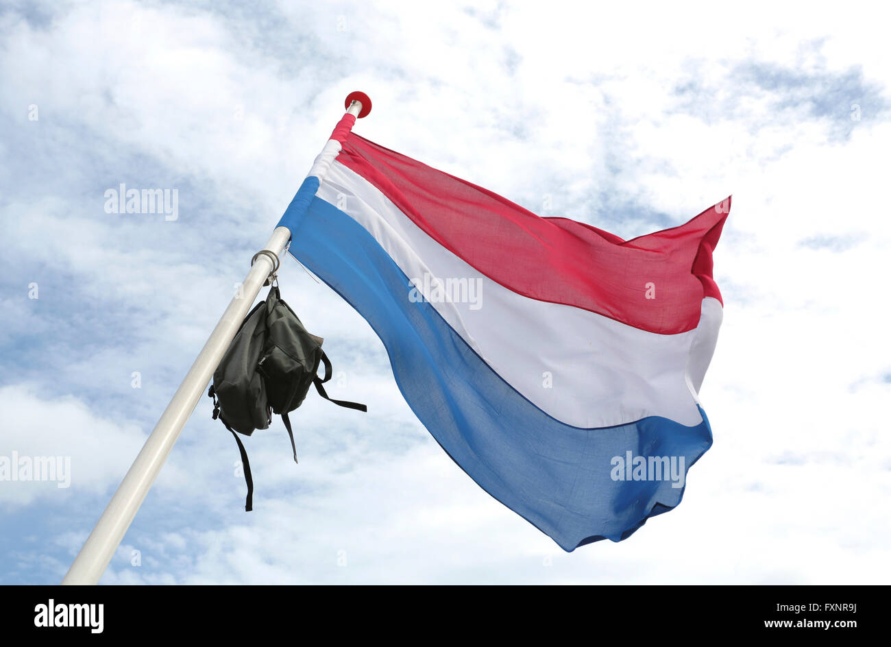 A dutch flag with a school bag in top to celebrate graduation - Stock Image