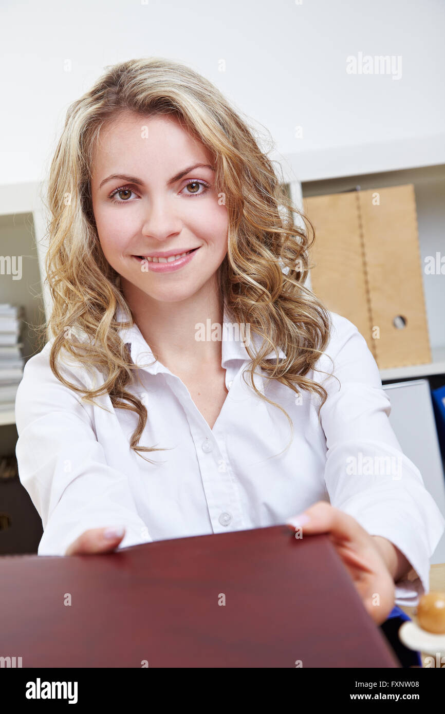 Attractive smiling woman offering application portfolio during a job interview Stock Photo