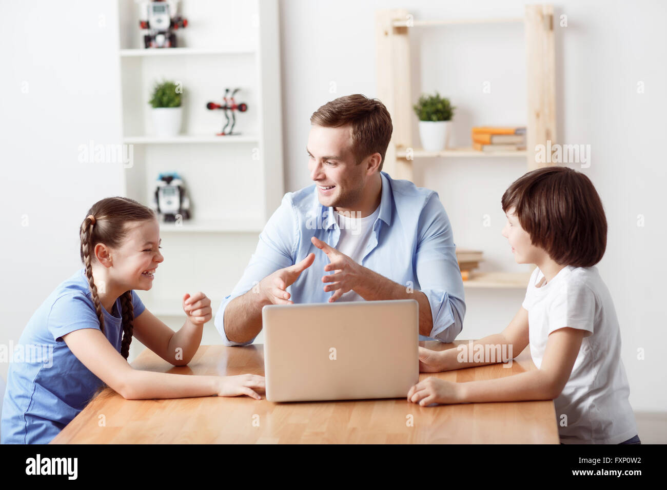 Positive father sitting at the table with kids - Stock Image