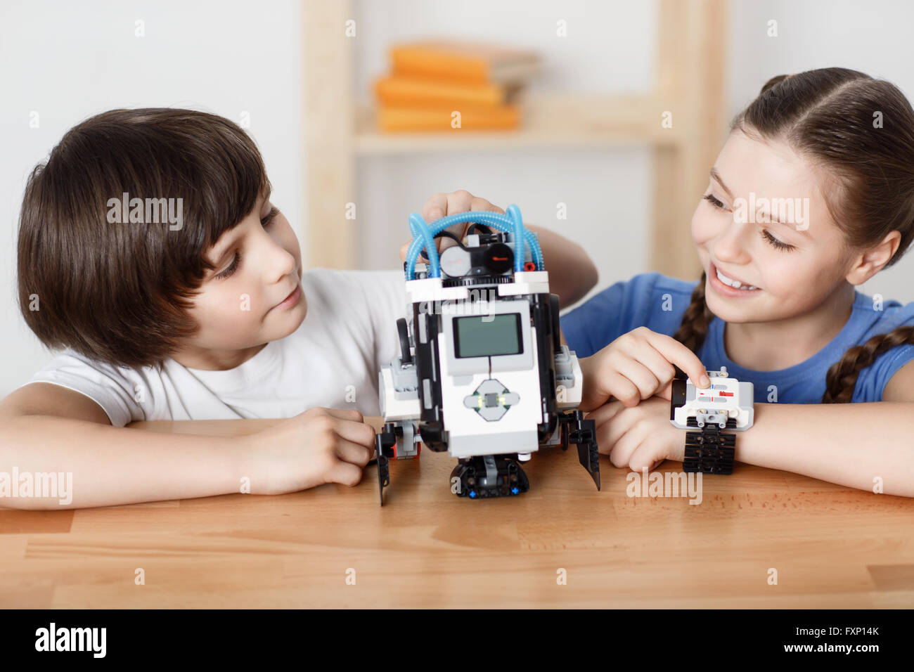 Positive children playing with robot - Stock Image