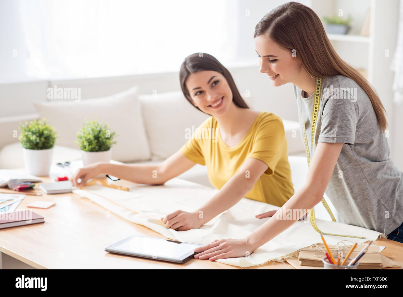 Nice seamstresses working at the table - Stock Image