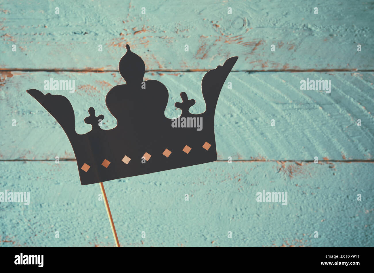paper fake crown in sticks in front of wooden background. vintage filtered image - Stock Image