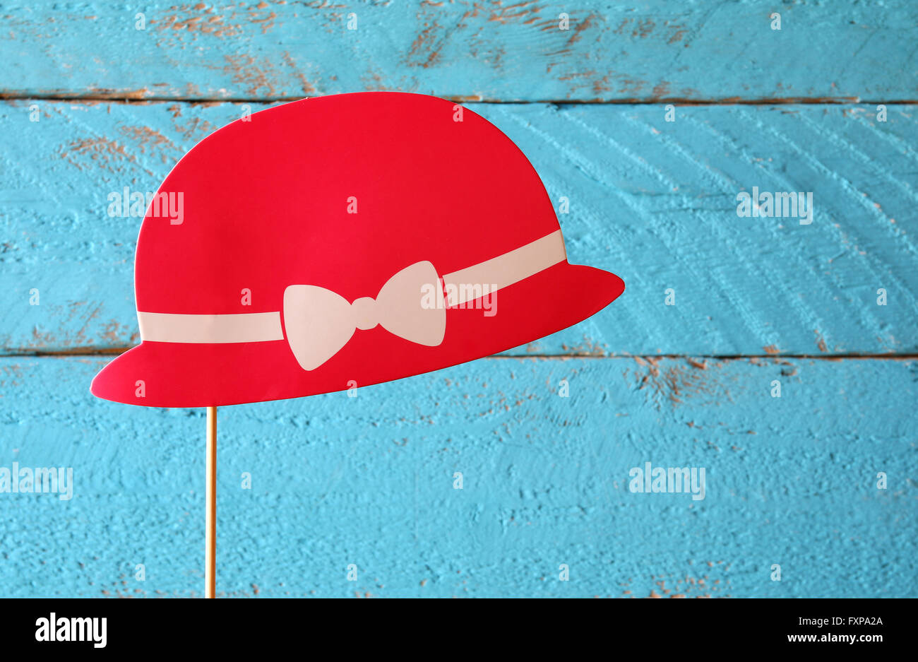 paper fake red hat in sticks in front of wooden background. vintage filtered image - Stock Image