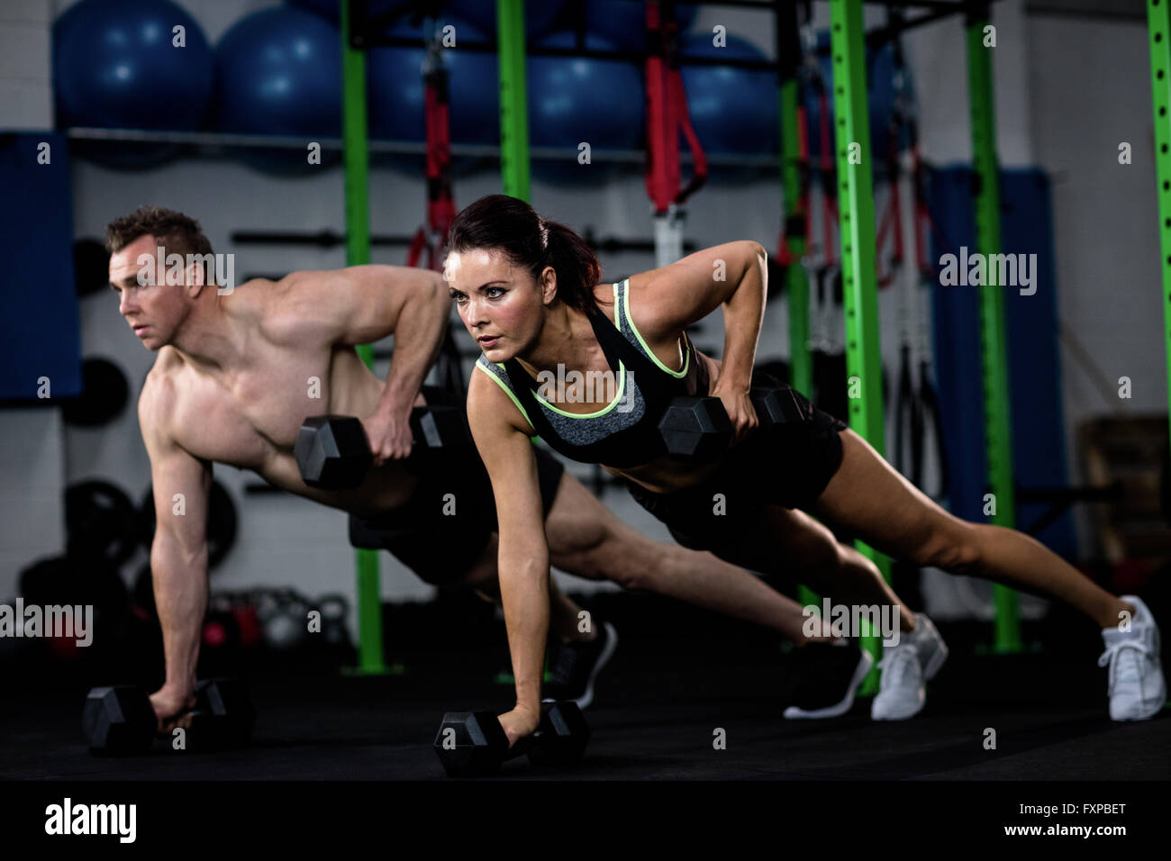 Man and woman exercising with dumbbell - Stock Image