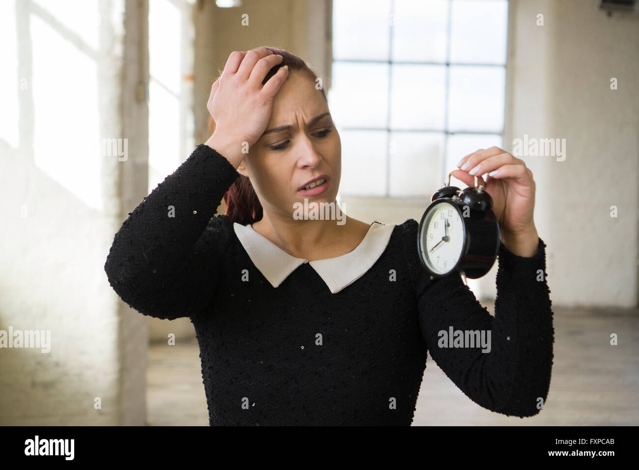 Annoyed woman looking at alarm clock - Stock Image