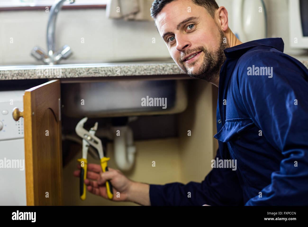 Portrait of plumber repairing a sink - Stock Image
