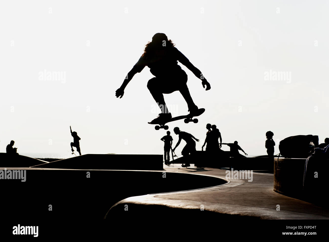 Skateboarder at skate park, silhouetted - Stock Image