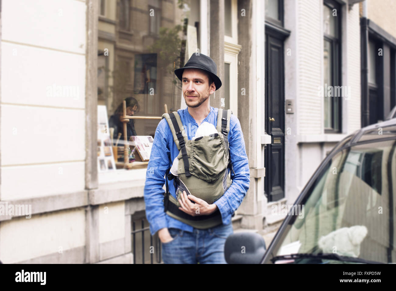 Man with baby in carrier on the move in the city - Stock Image