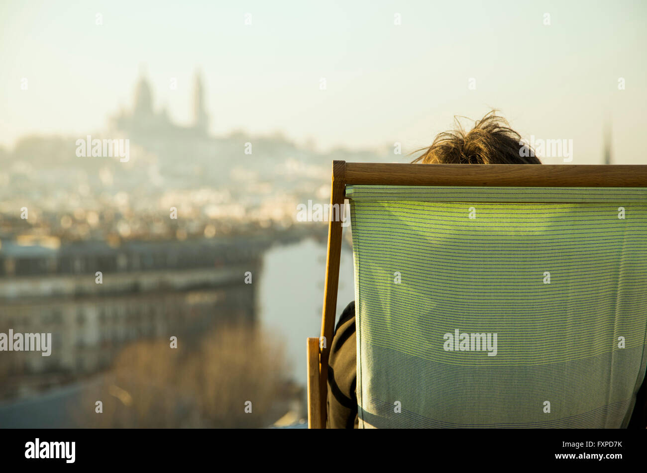 Person sitting in deckchair, looking at view of city - Stock Image