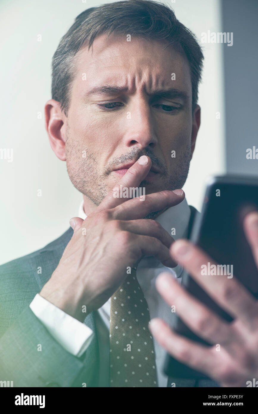 Businessman looking at digital tablet with furrowed brow - Stock Image