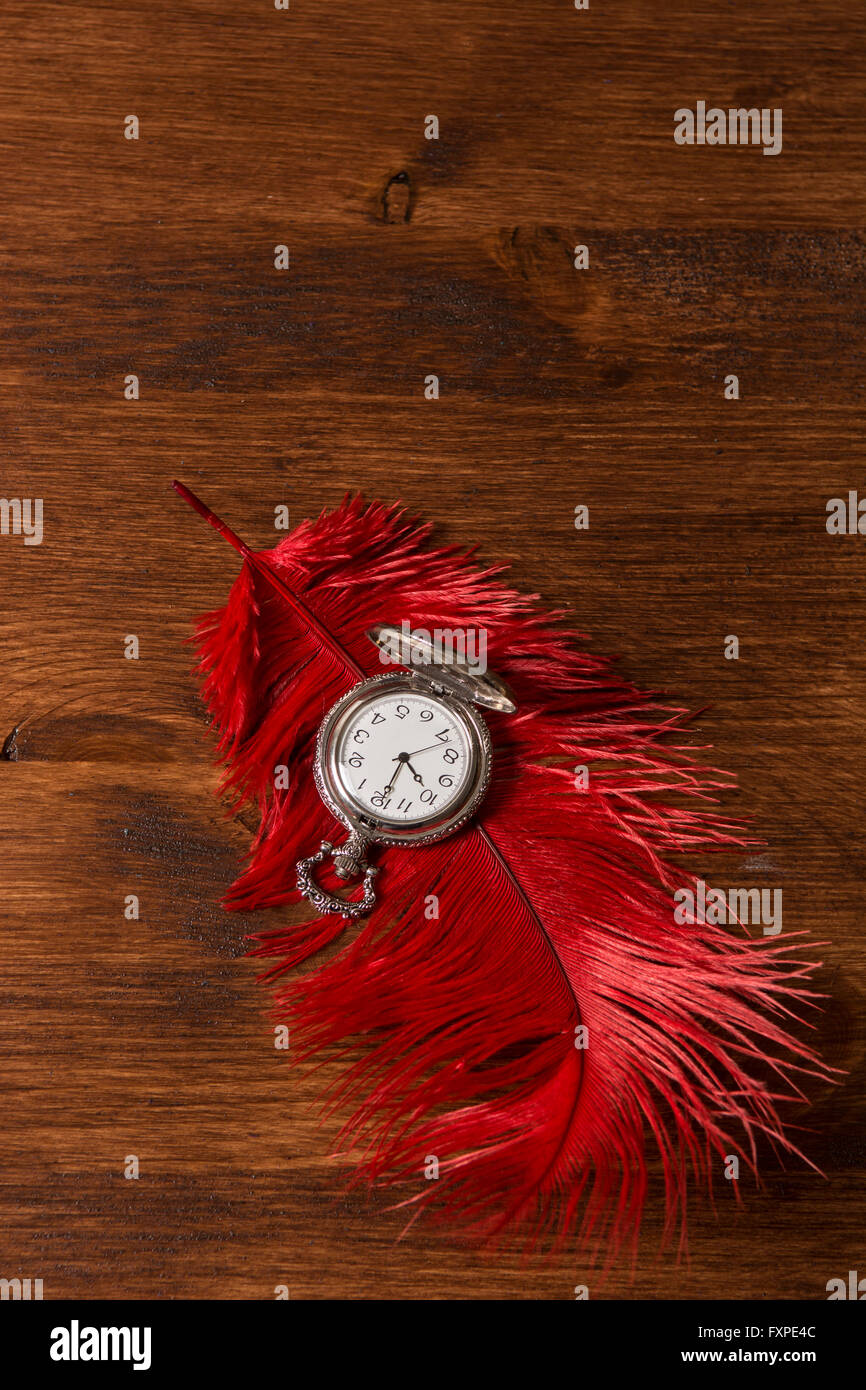 Vintage pocket watch over a red feather - Stock Image