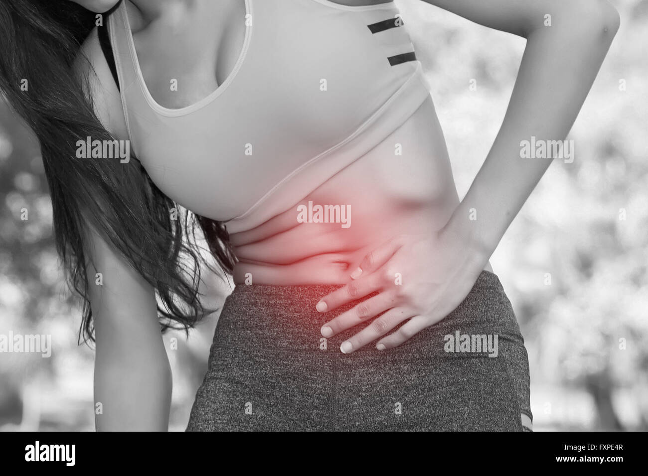 Woman in sport bra having a stomachache / food poisoning / stomach problems / womb problems / menstruation pain - Stock Image