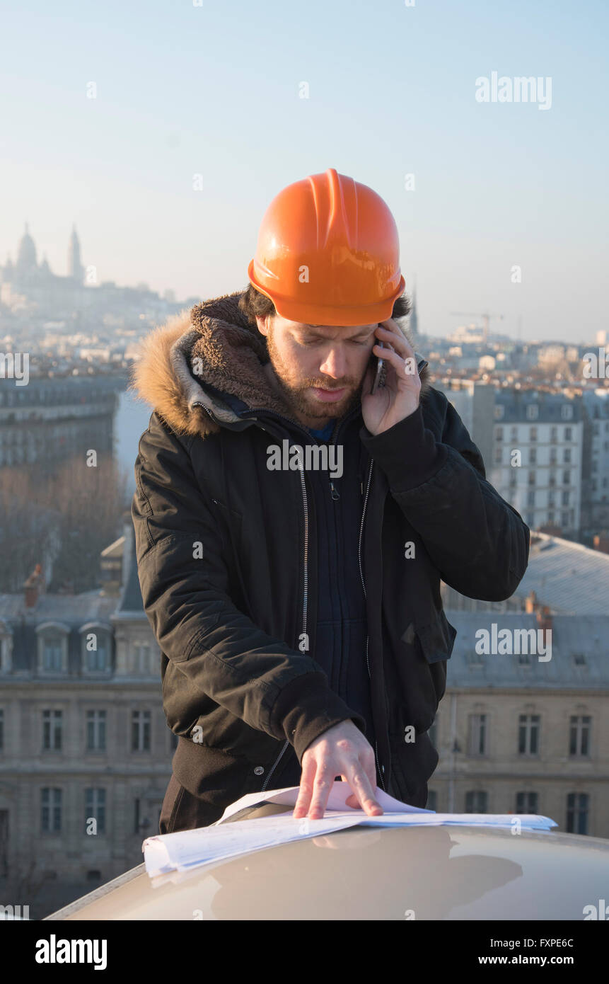 Construction supervisor talking on cell phone and looking at blueprints - Stock Image