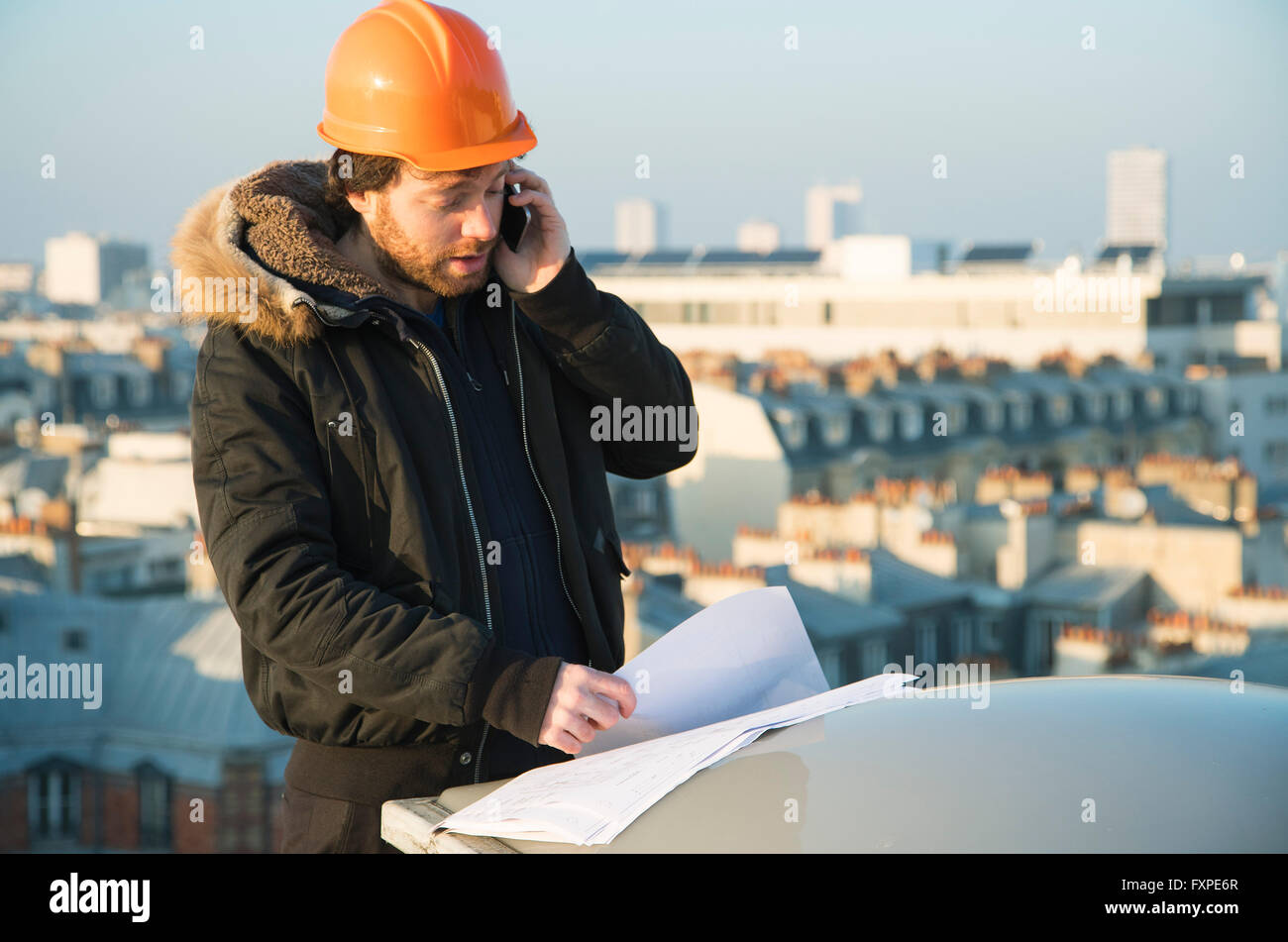 Construction supervisor studying blueprints and talking on cell phone - Stock Image