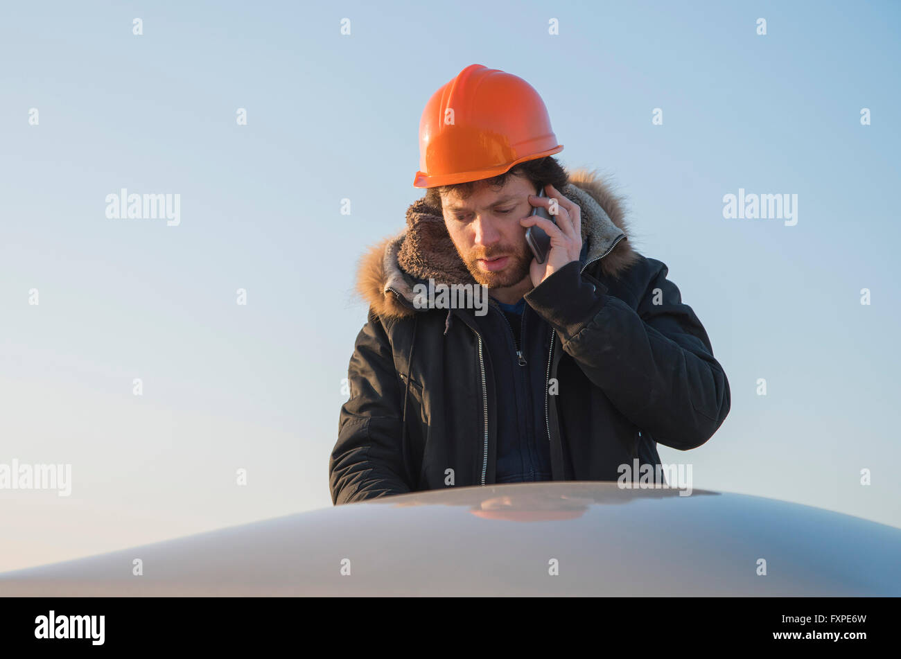 Construction worker talking on cell phone - Stock Image