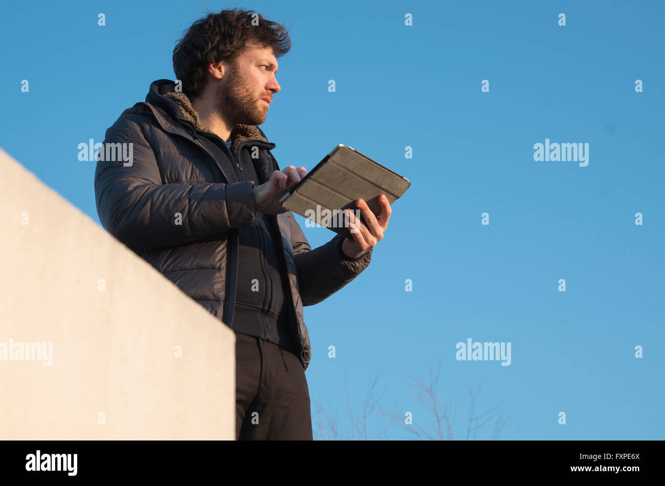 Man holding digital tablet outdoors, looking away in thought - Stock Image