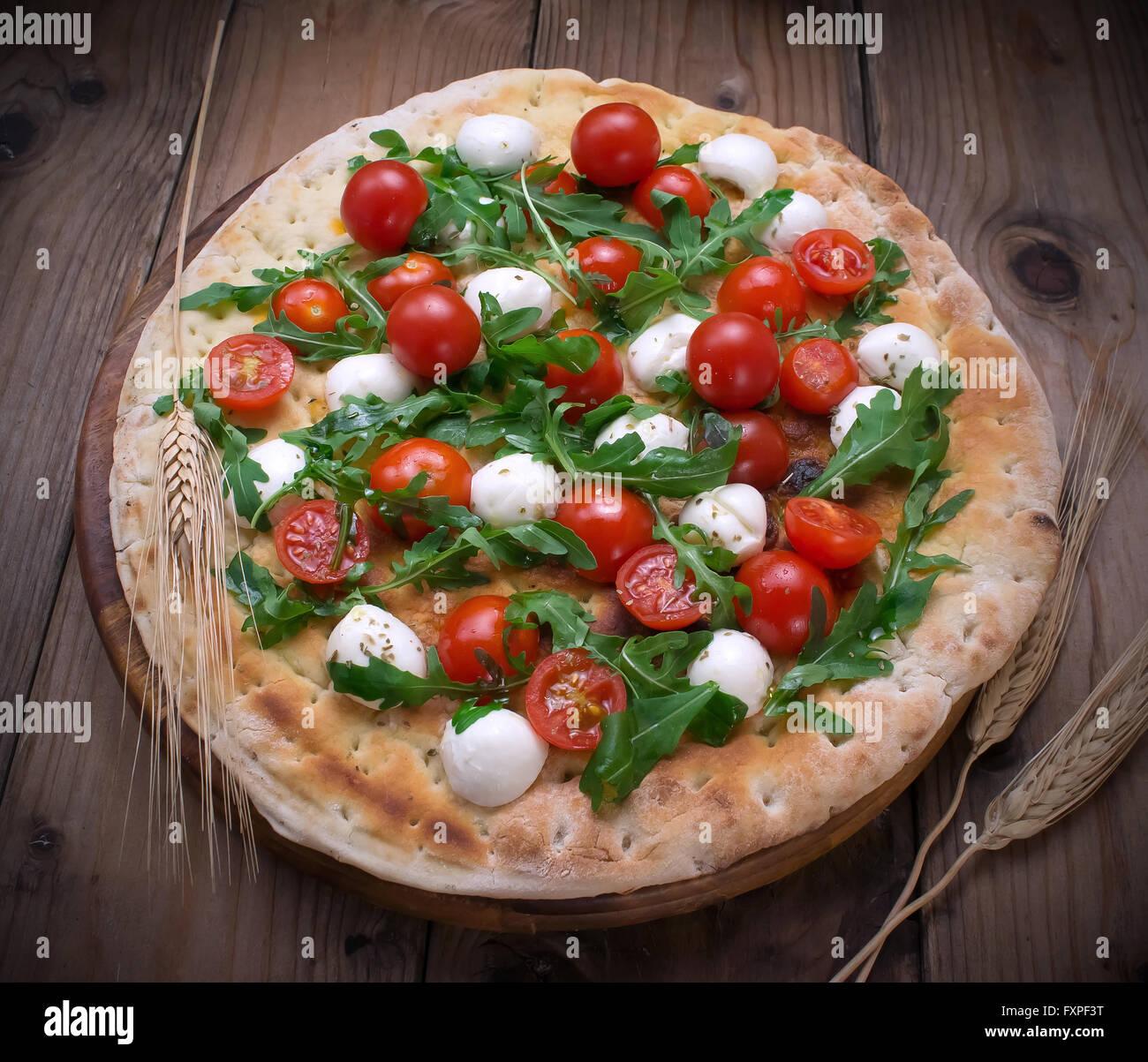Italian focaccia with fresh organic cherry tomatoes and rocket salad - Stock Image
