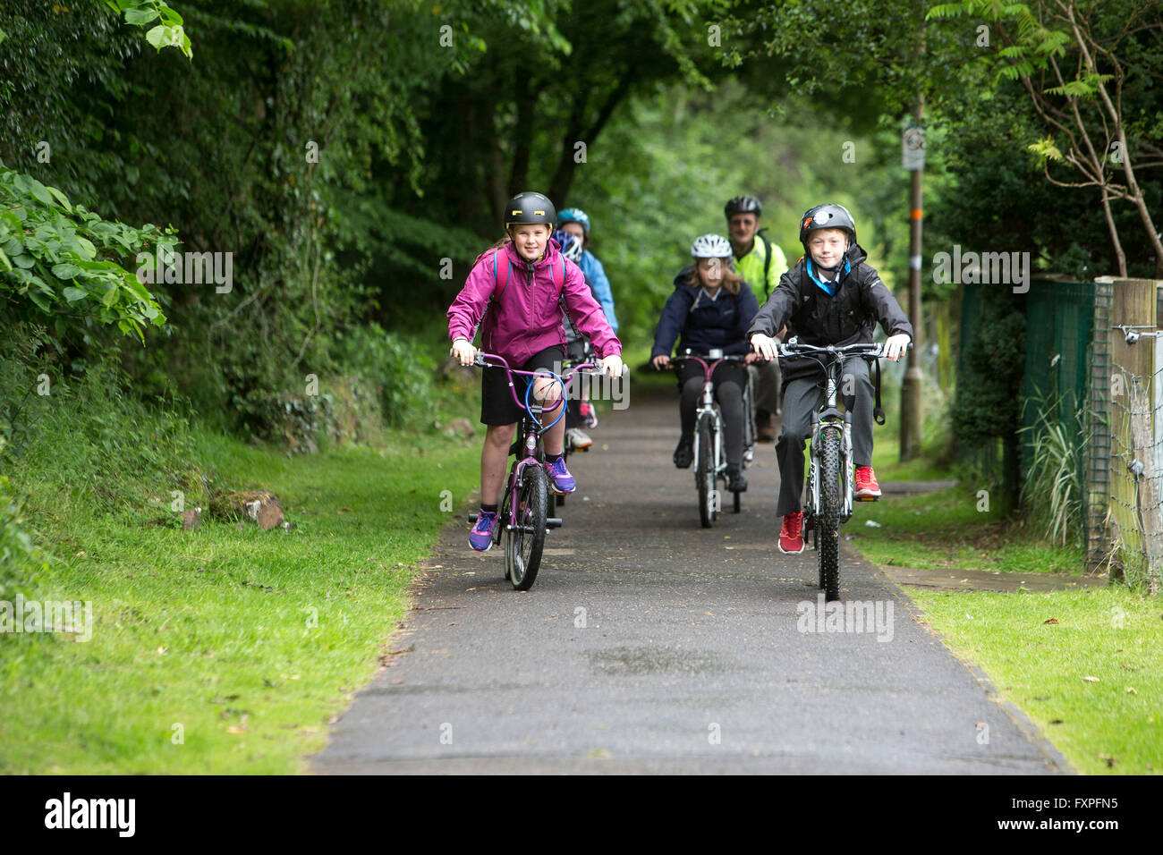 Children safely cycling to school with adult supervision on pathways - Stock Image