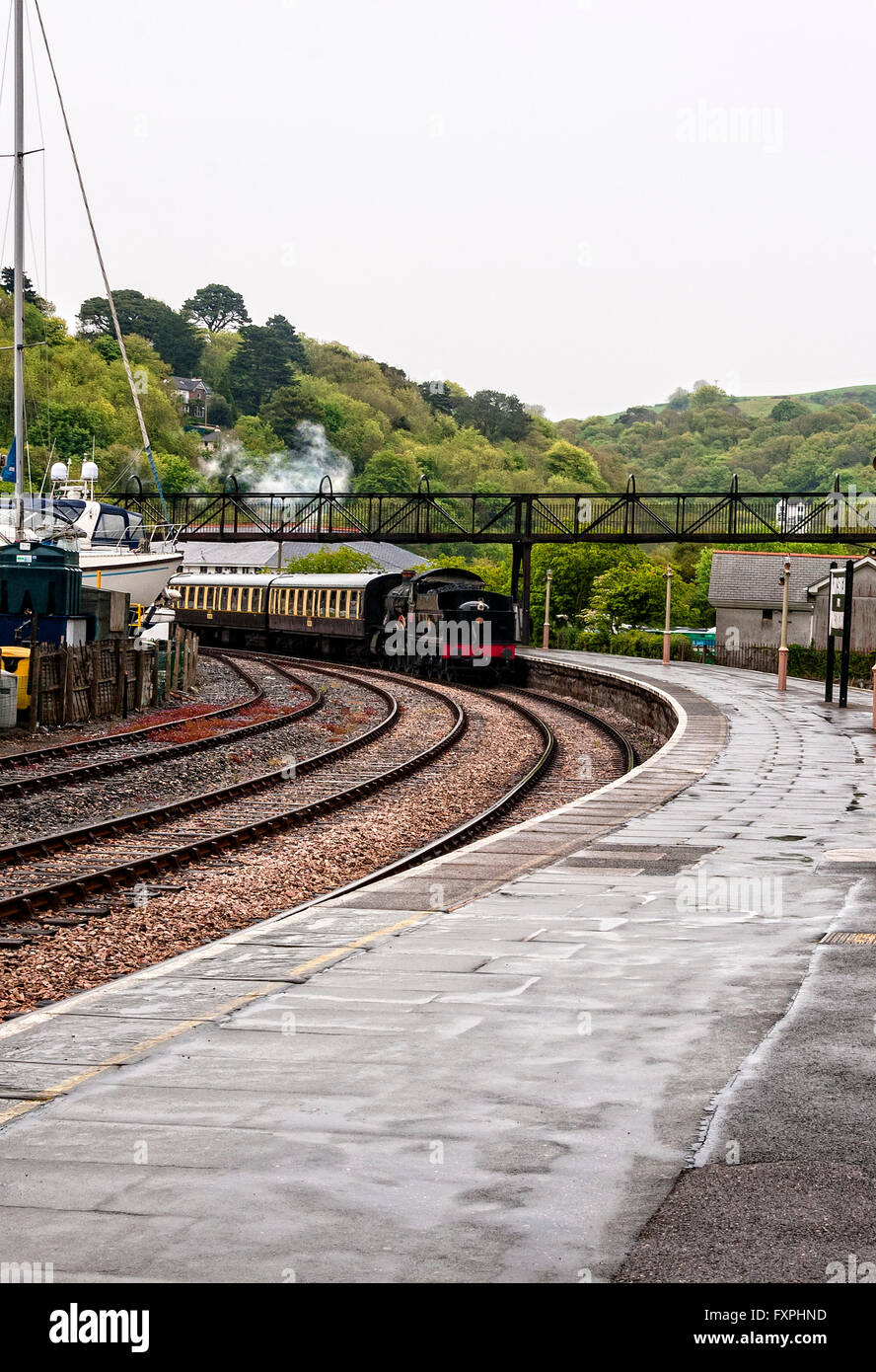 The restored passenger train Lydham Manor gleams as it hauls coaches around a bend alongside the platform of Kingswear - Stock Image