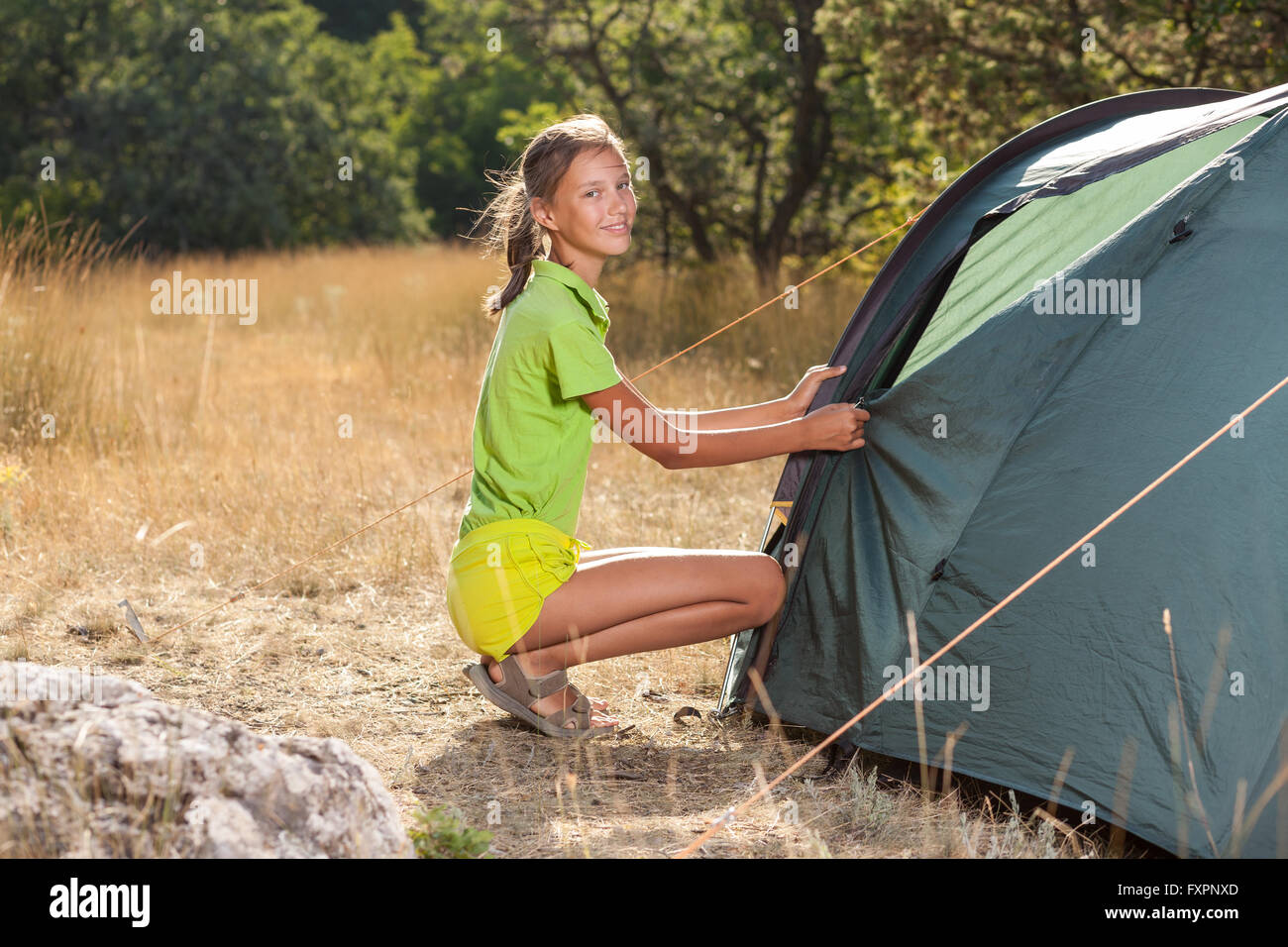 Smiling teenager girl setting a tent - Stock Image