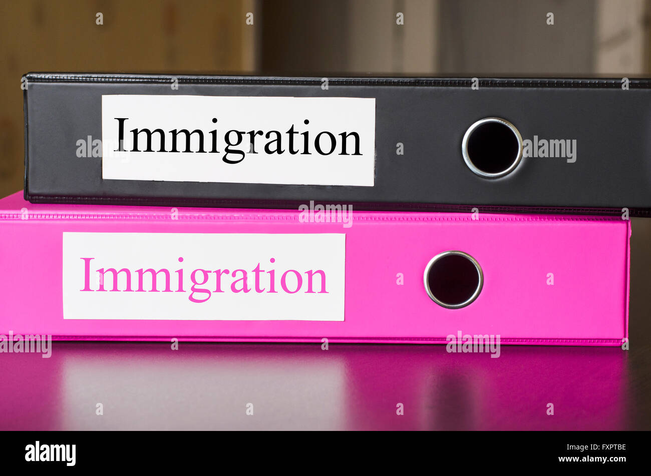 Bright office folders over dark background and immigrations text concept - Stock Image