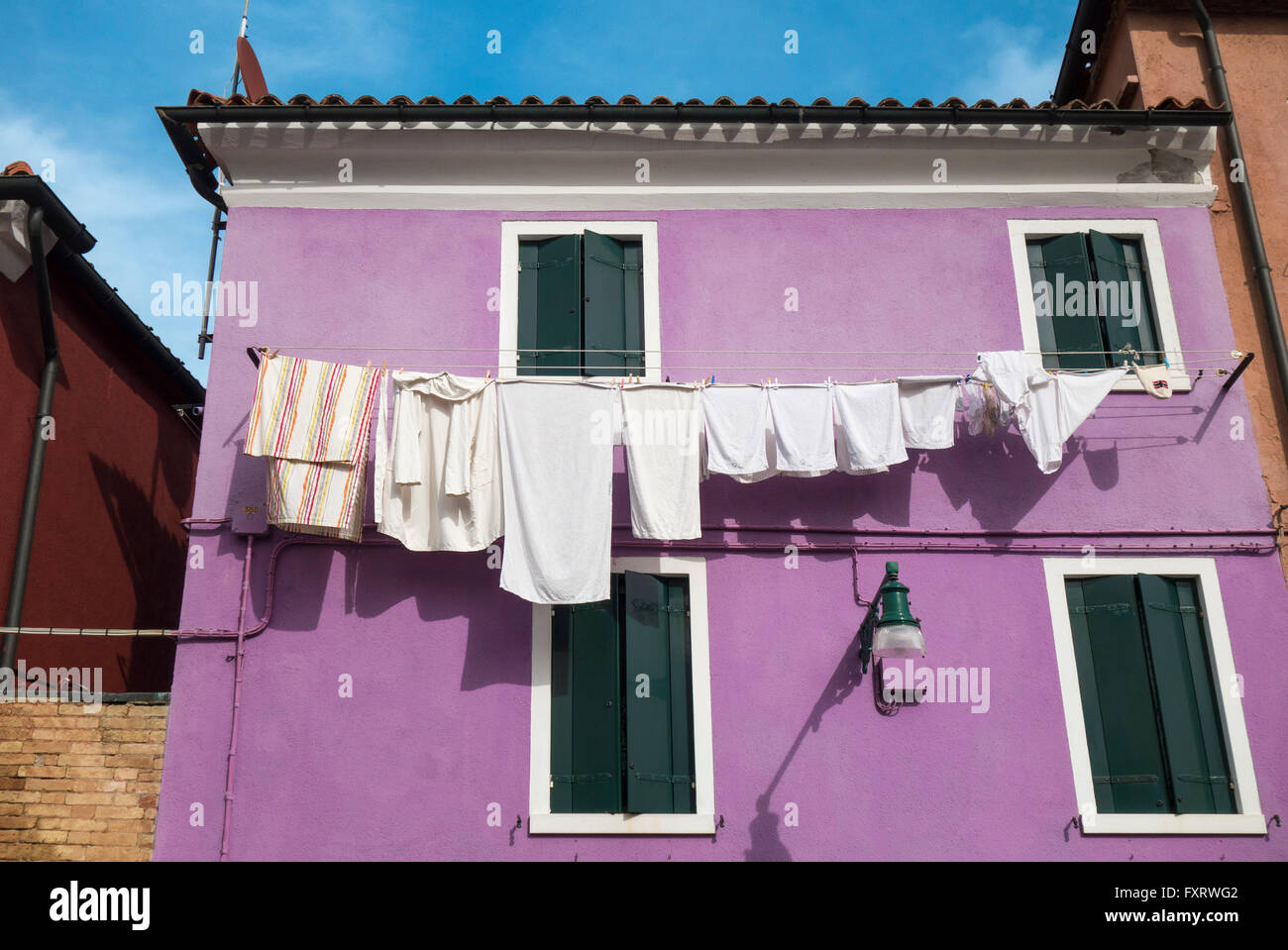 Venice - Island of Burano colorful colourful house with clothesline clothes line along the Canal. - Stock Image