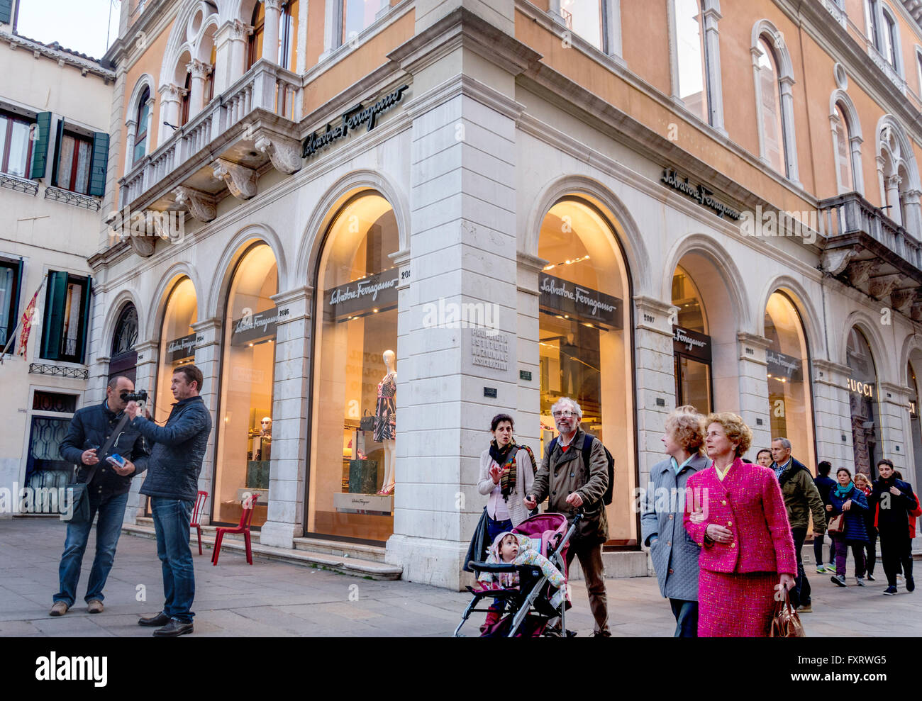 Venice Italian people locals and tourists shopping. Man pushing baby stroller in front of Ferragamo and Gucci fashion - Stock Image