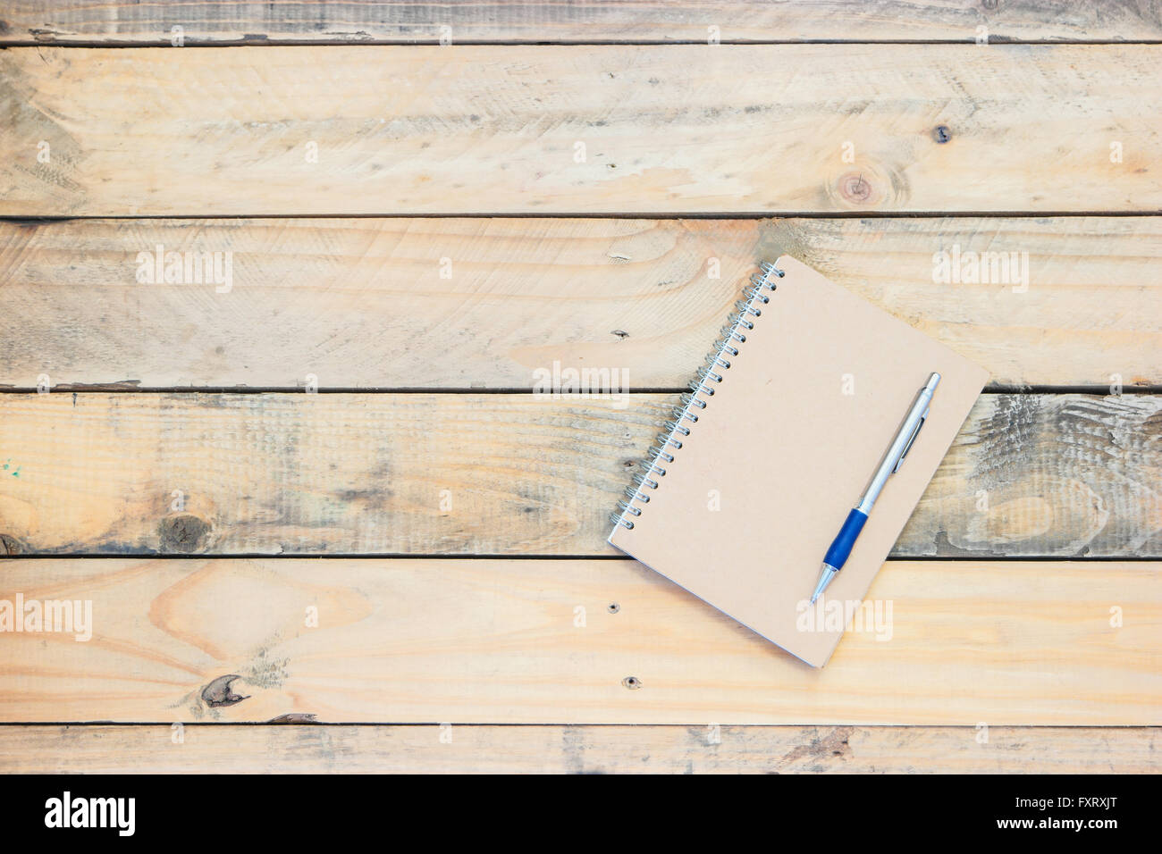 Vintage style of notebook and pen on the old wooden floor. Stock Photo