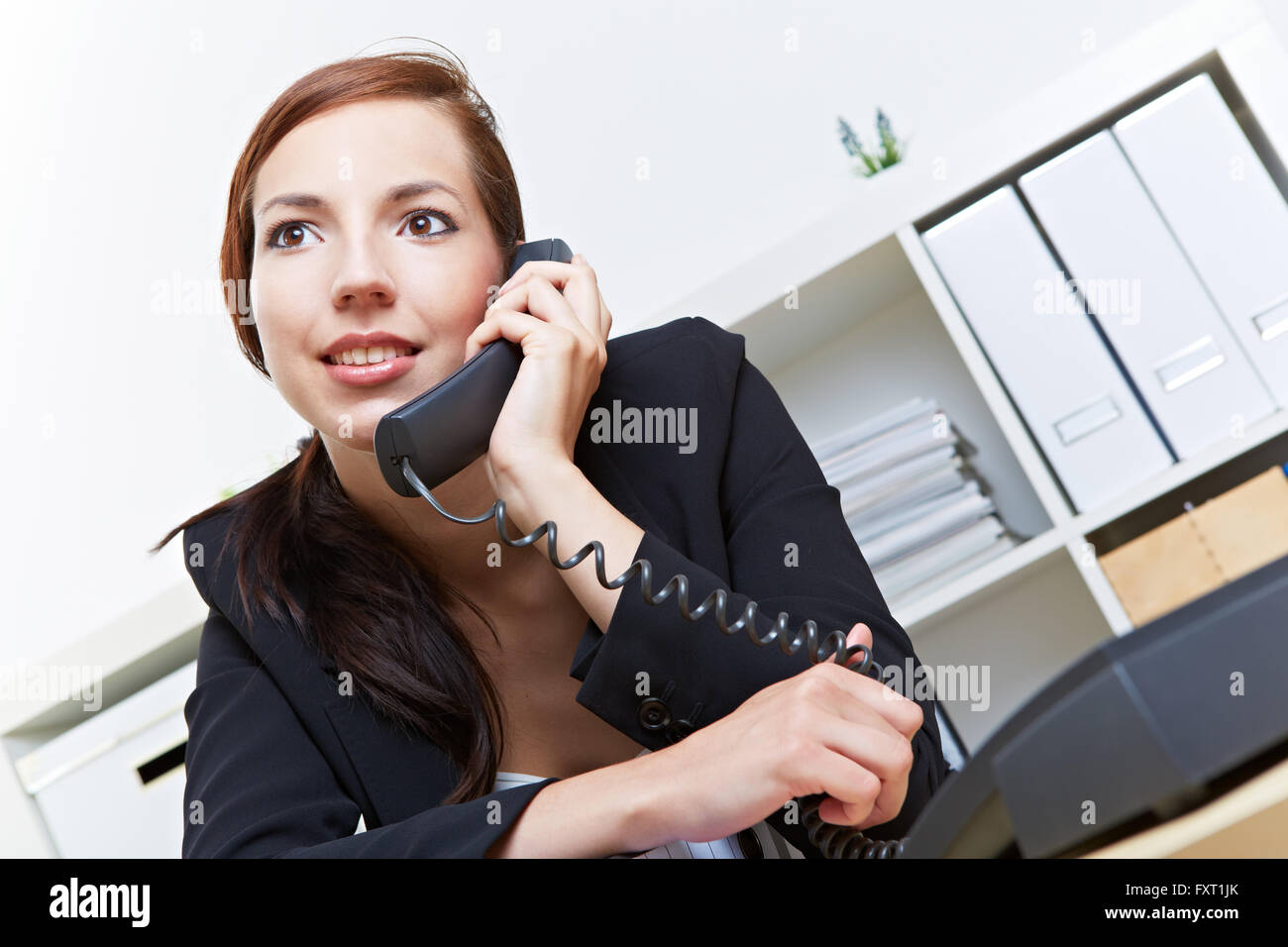 Smiling secretary using the phone in the office for a call - Stock Image