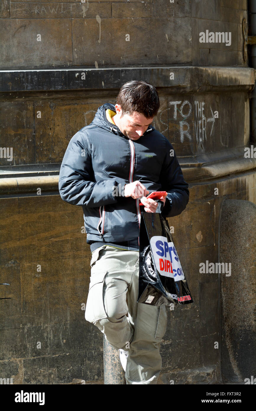 Man leaning against wall checking smart phone holding Sports Direct  shopping bag in Cambridge, Cambridgeshire, England 8fd23eae84