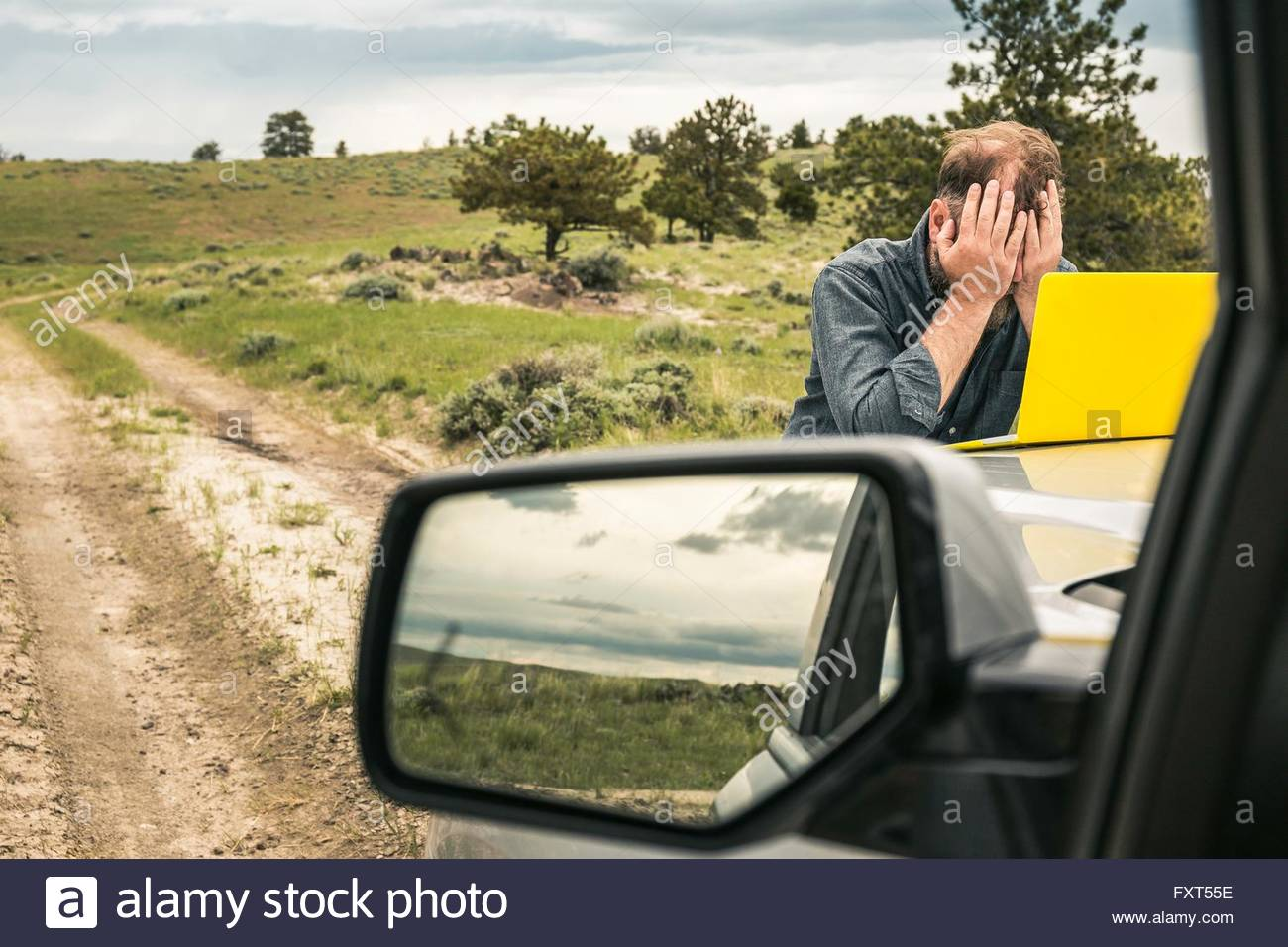 Man on dirt track road trip with head in hands at car bonnet, Cody, Wyoming, USA - Stock Image